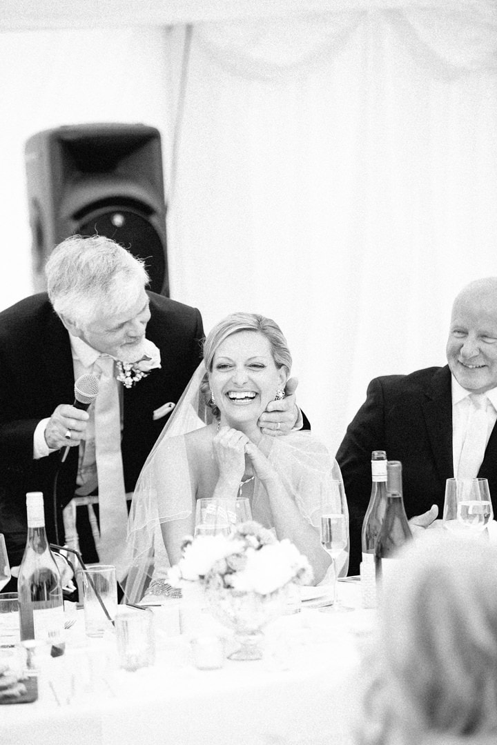 bride laughing at wedding reception black and white