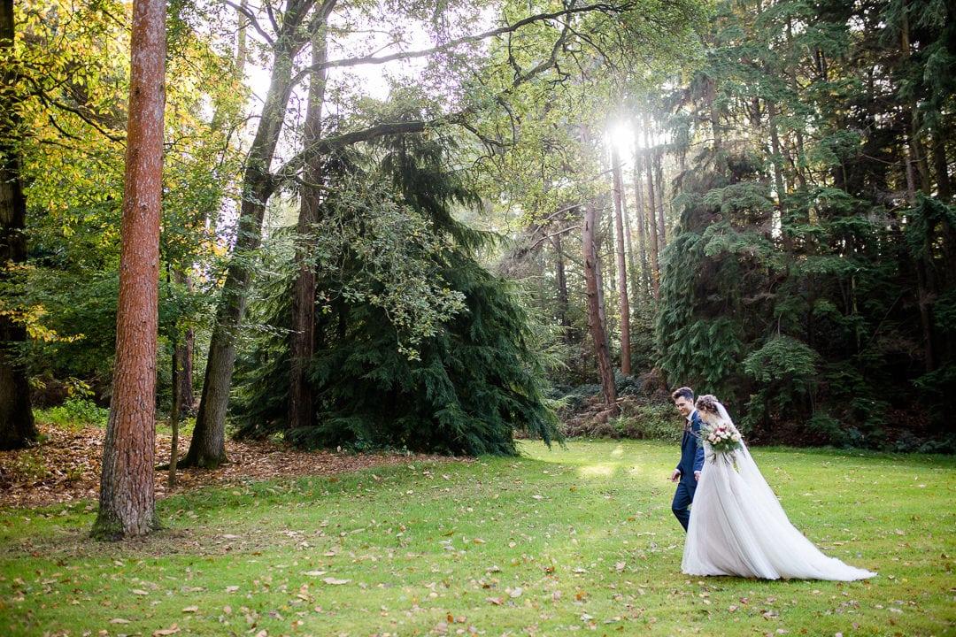 bride and groom walking in woods