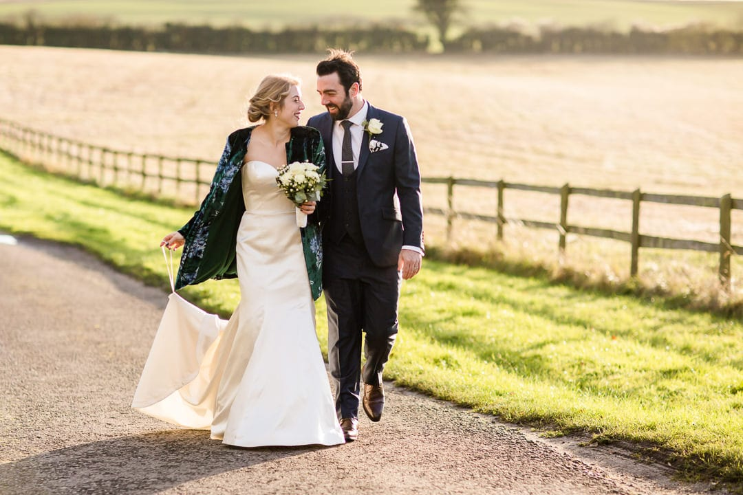 bride and groom walking in sunset at Clock Barn