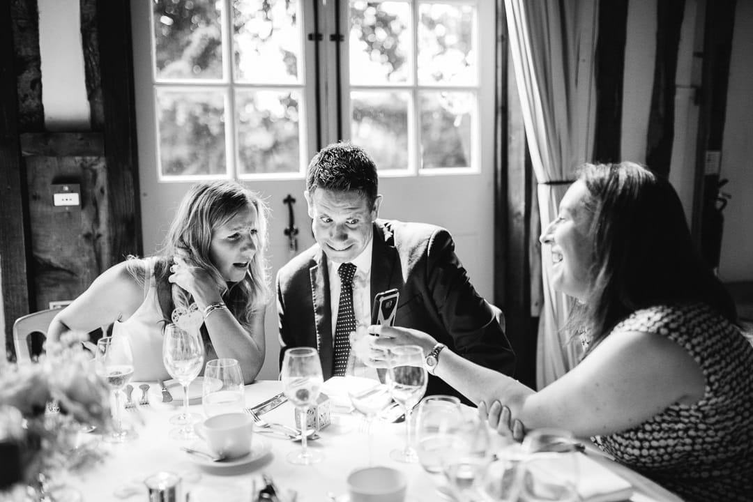 wedding guests looking at phone