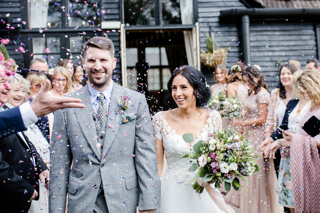 bride and groom in confetti throw at Clock Barn Hampshire