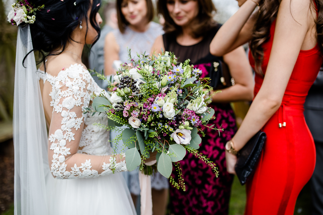 bride's bouquet and lace dress sleeve