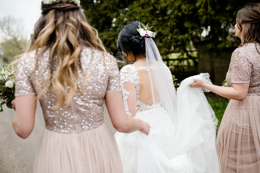 key hole back of wedding dress, bridesmaids holding tulle train