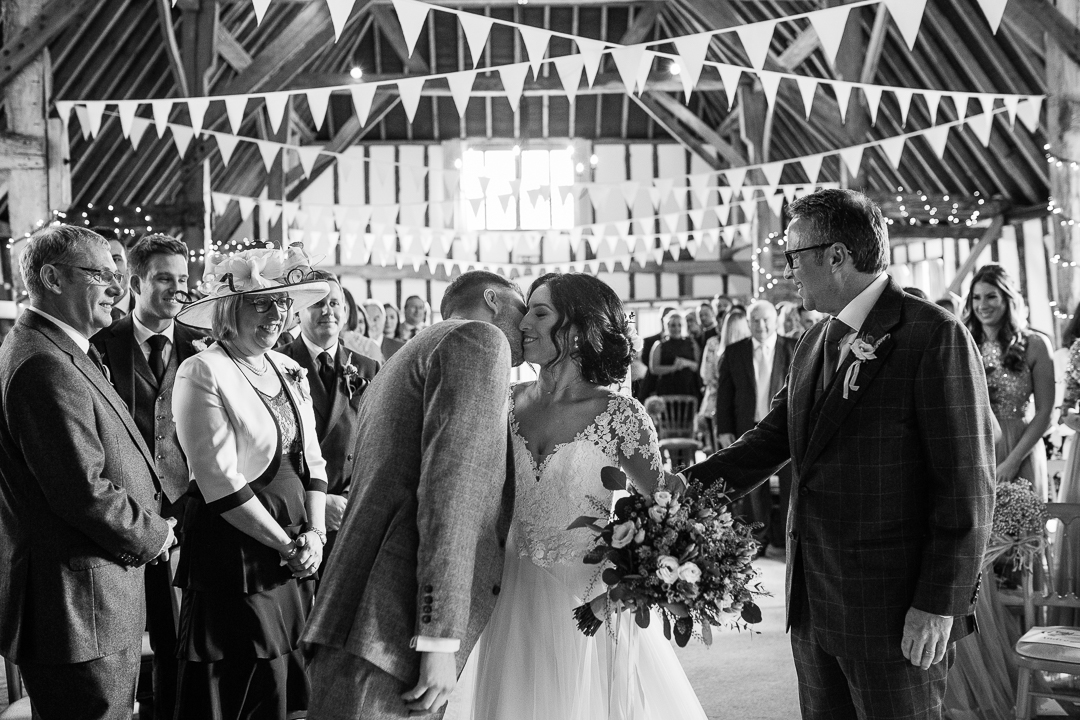 bride and groom embrace during ceremony at Clock Barn Hampshire