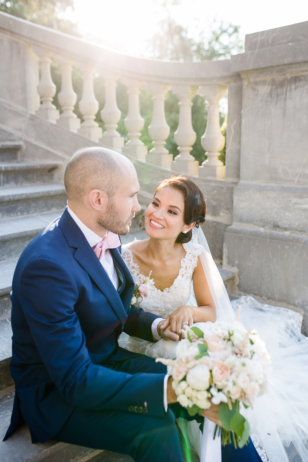 bride and groom sat on the stairs outside chateau bouffemont paris france image