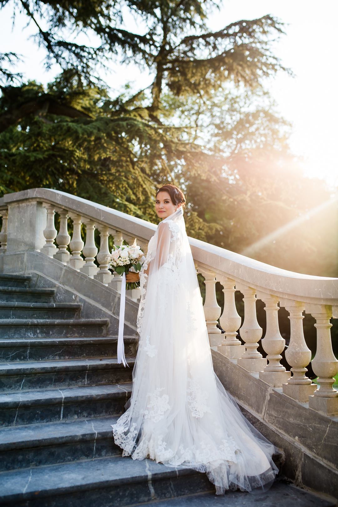 bride standing on the steps at chateau bouffemont at sunset image