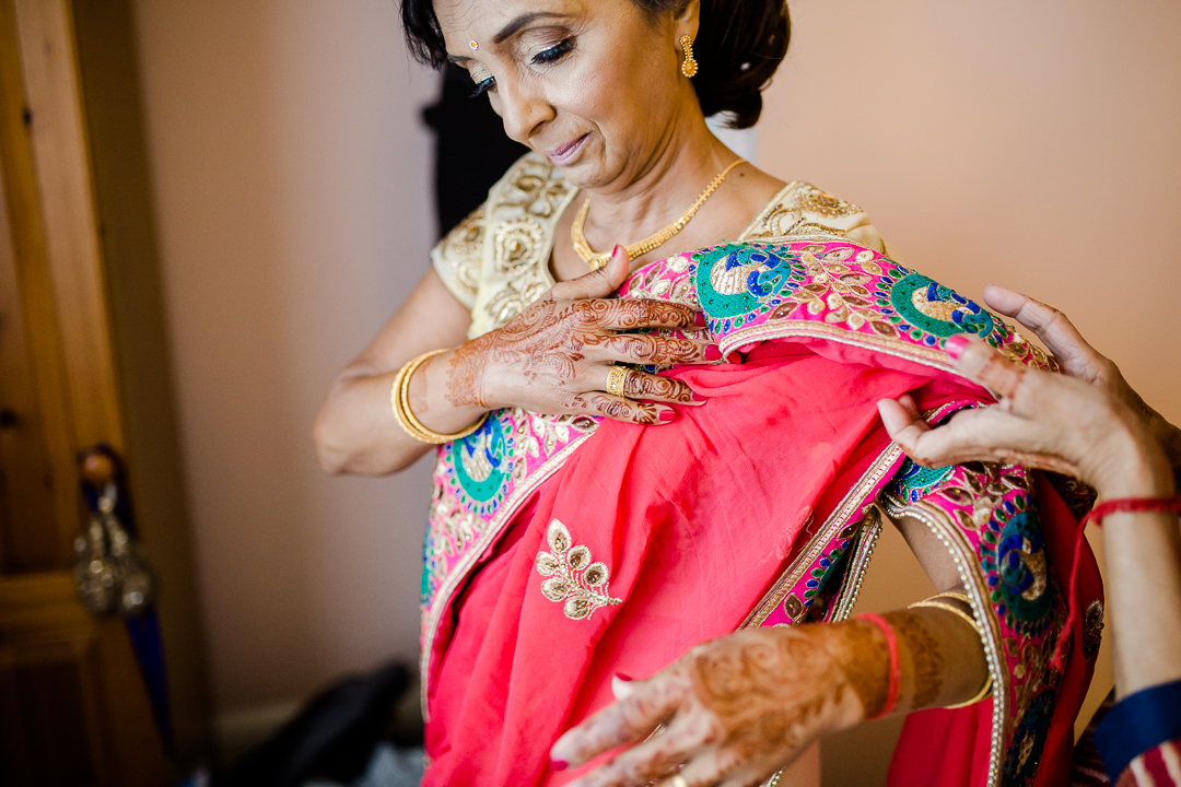 Asian mother of the bride dressing in a pink and gold sari for her daughters Hindu wedding ceremony