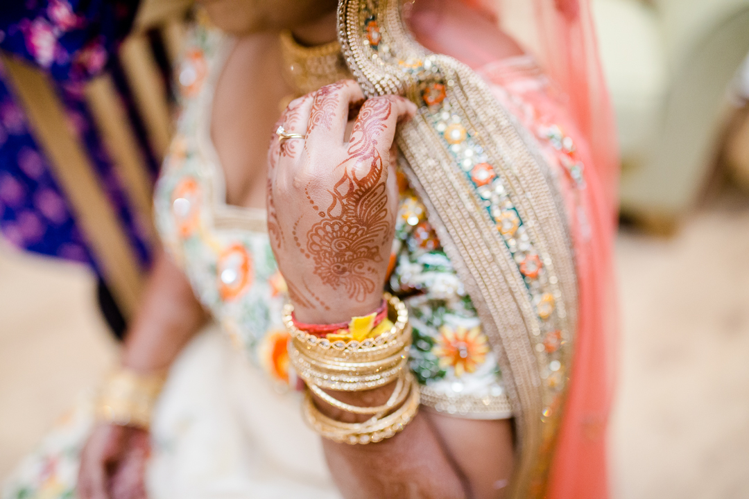 close up image of mehndi henna & golden bangles on a bride's hands