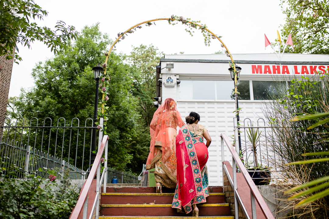 bride and her mother walk the steps to temple for hindu wedding in Lewisham