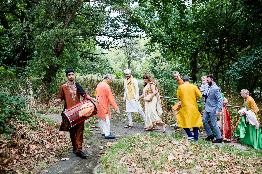 Groom before Hindu wedding with his family walks with drummer