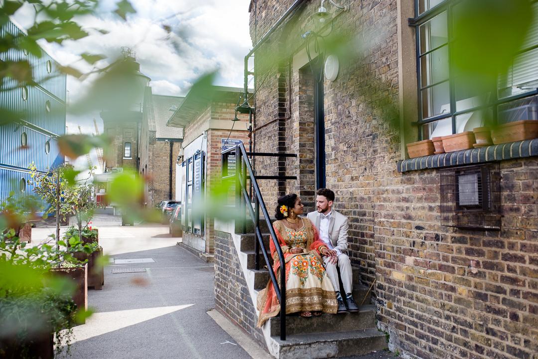 bride and groom sit on some steps in an urban area near Trinity Bouy Wharf wedding venue London