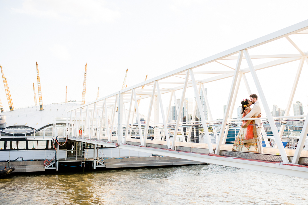 bride and groom kissing on a docklands bridge near Trinity Bouy Wharf at sunset with the millennium dome and London skyline behind them