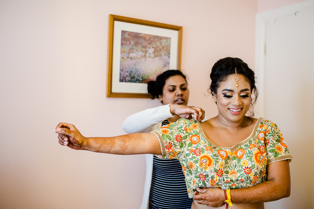Asian bride being dressed in a sari for her hindu wedding