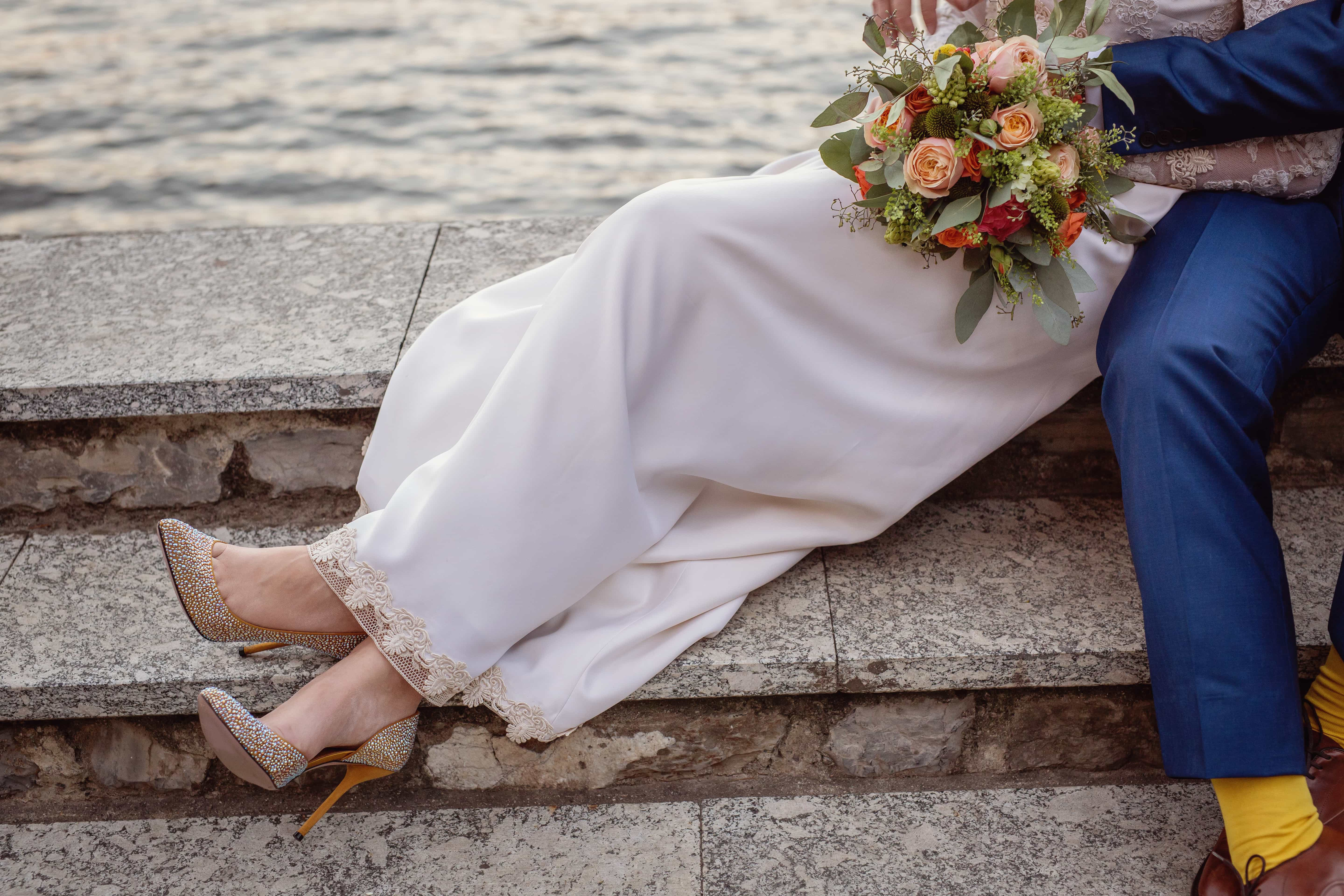 close up glitter wedding shoes bouquet and flowing dress