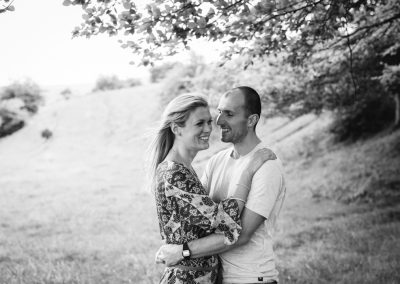 couple smiling in field for engagement photo