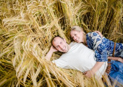 engagement photo couple lying in long grass