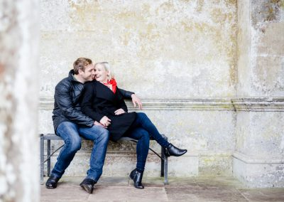 couple sitting by old building for engagement