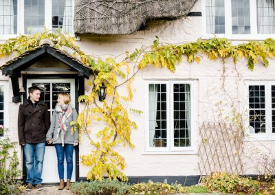 engaged couple in country cottage doorway