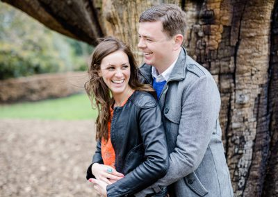 engaged couple laughing by tree for photoshoot
