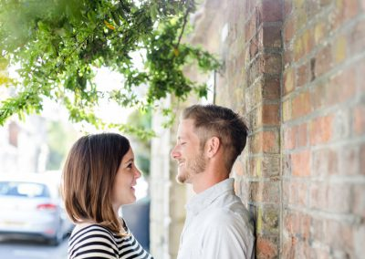 engagement photoshoot couple leaning on wall in sun