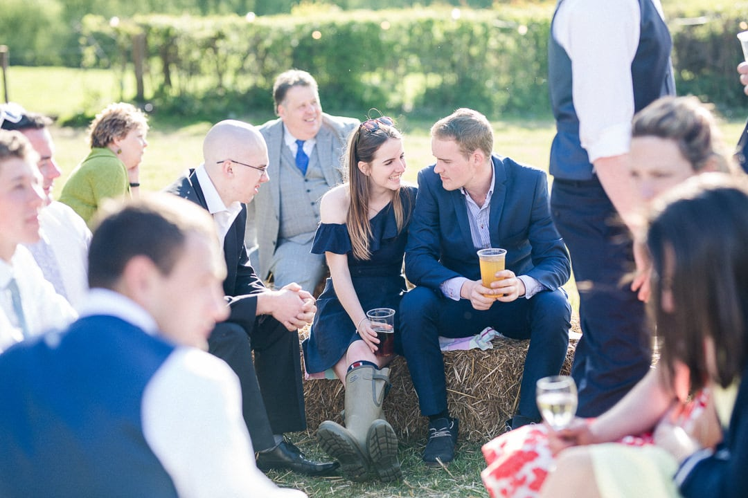 guests relaxing on hay bayles at wedding