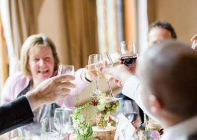 guests clinking glasses at wedding