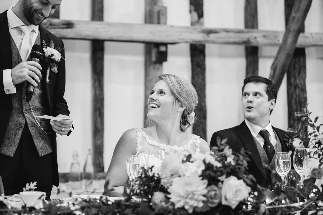 bride smiling during wedding speeches