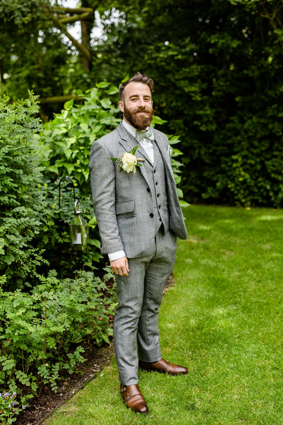 groom in a grey three piece suit with bow tie and a beard