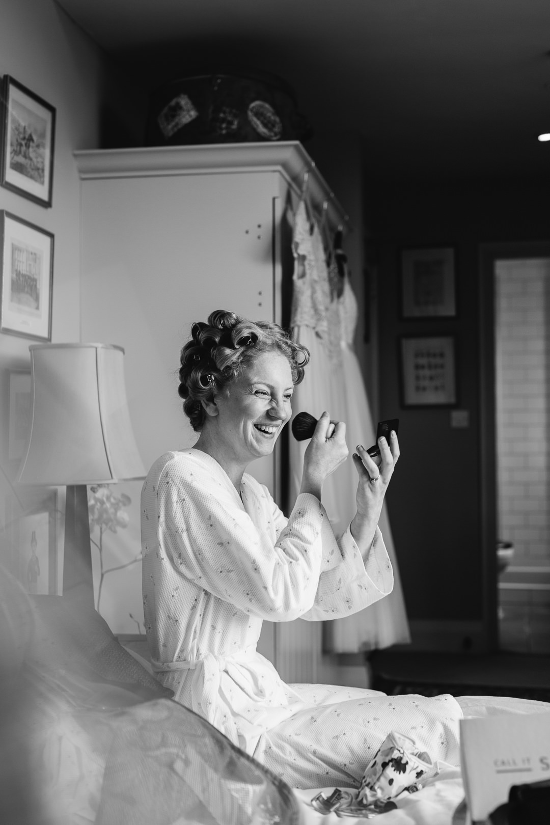 bride putting on blusher with brush and hair in curlers