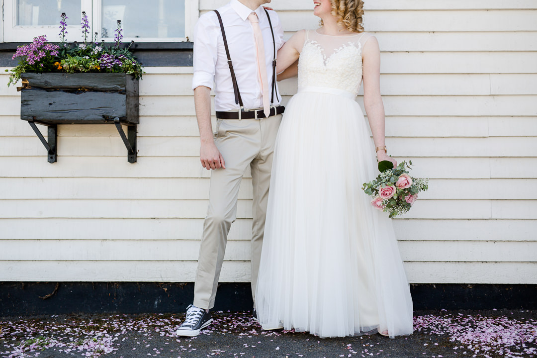 groom wearing braces and converse and bride with tulle skirt leaning against a wall