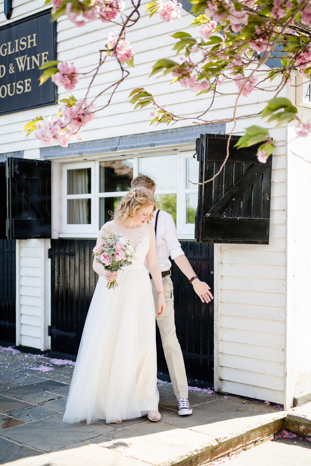 bride and groom at the anchor inn lower froyle with blossom