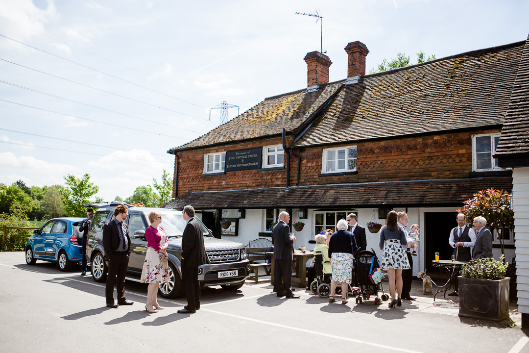 guests standing outside of the anchor inn lower froyle before a wedding