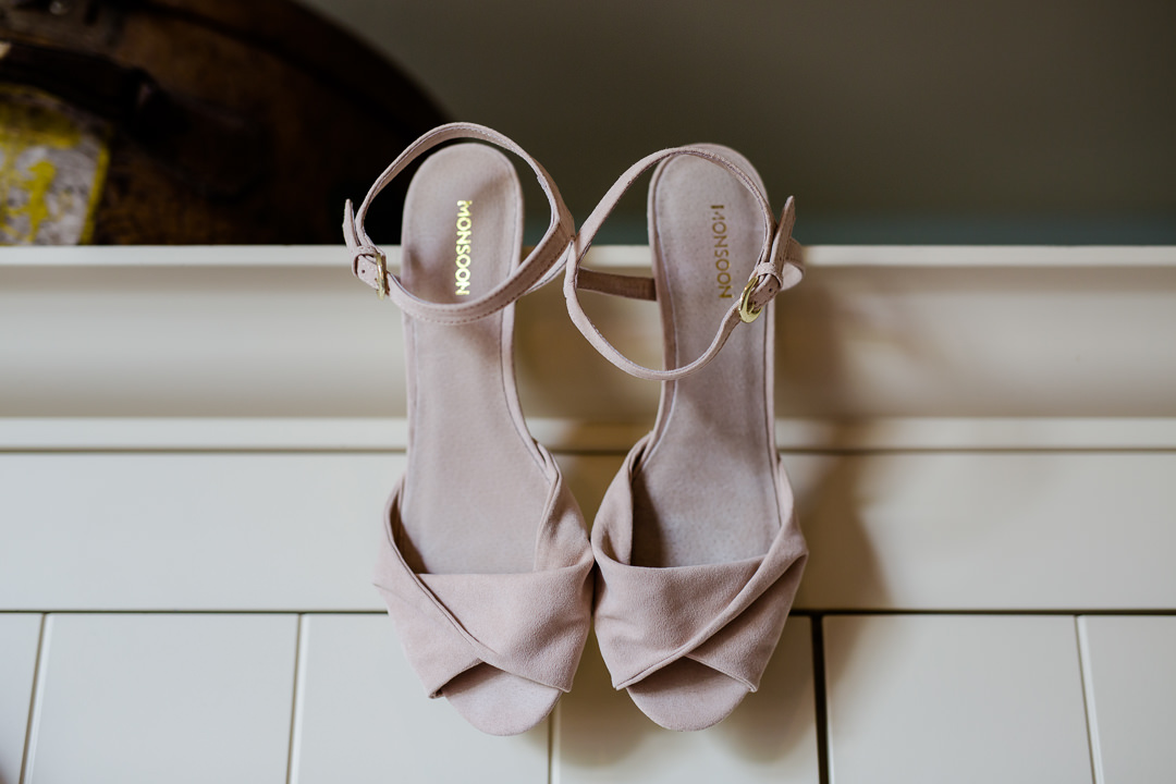 pink suede shoes hanging from wardrobe