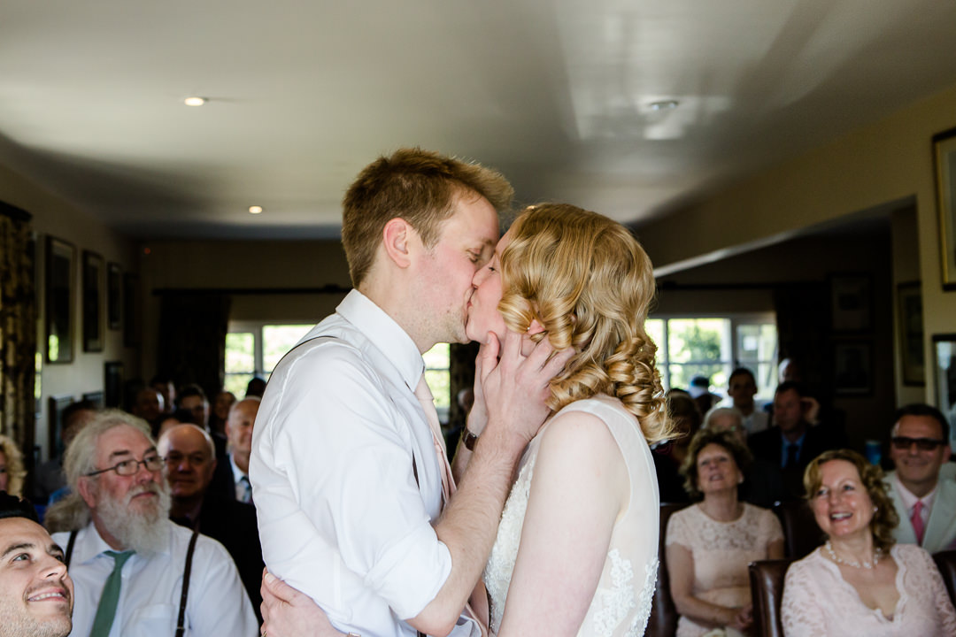bride and groom first kiss at the anchor inn lower froyle wedding