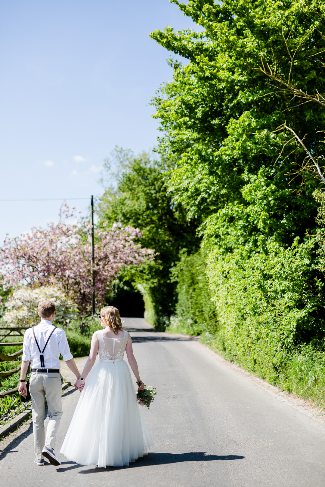 bride and groom walking down country lane in Hampshire England