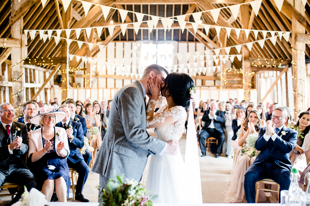 bride and groom's first kiss at Clock Barn Hampshire