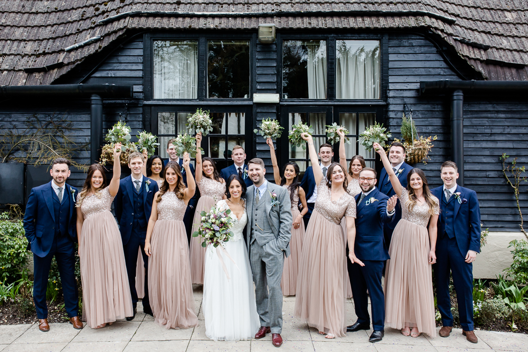bridal party of groomsmen and bridesmaids with the bride and groom at Clock Barn Hampshire
