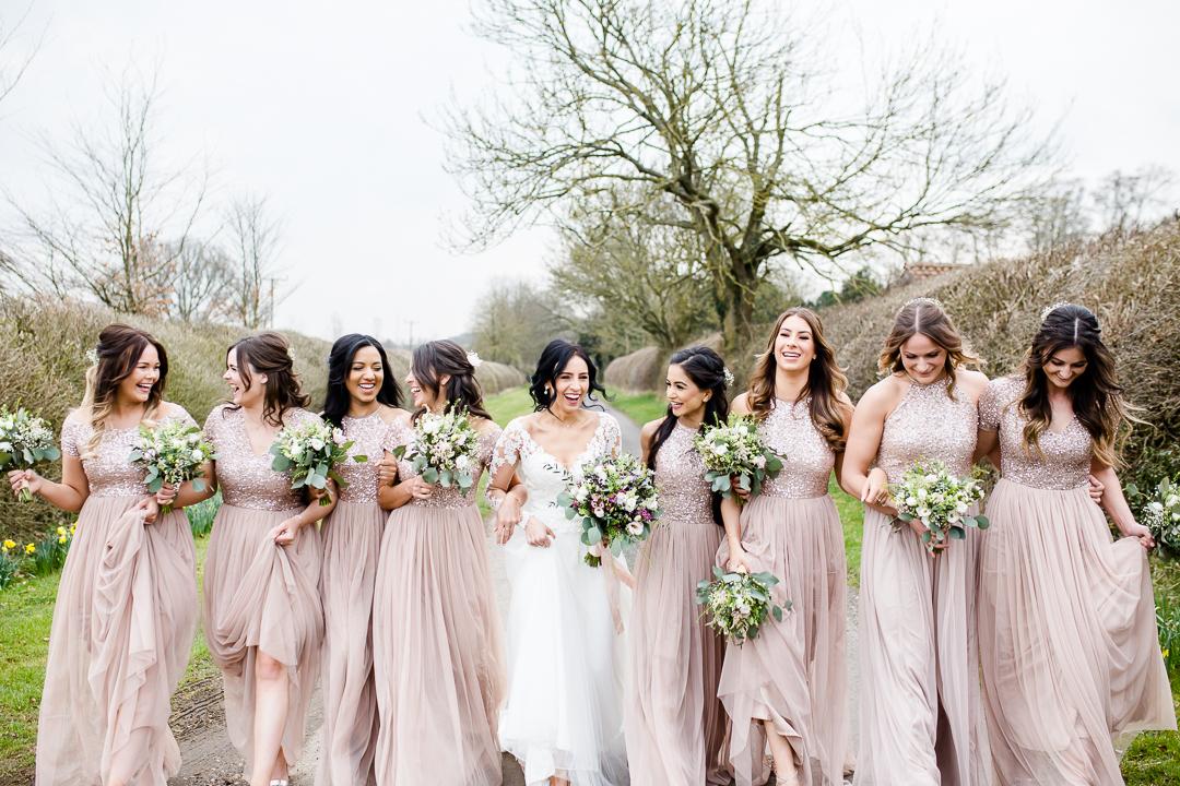 bride and bridesmaids walking at Clock Barn Hampshire