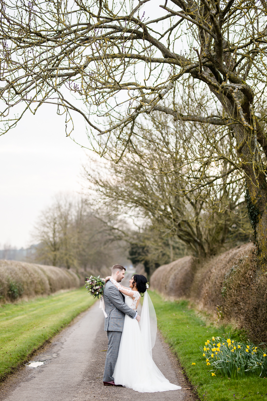 bride and groom hug in a lane under an arch of trees with daffodils