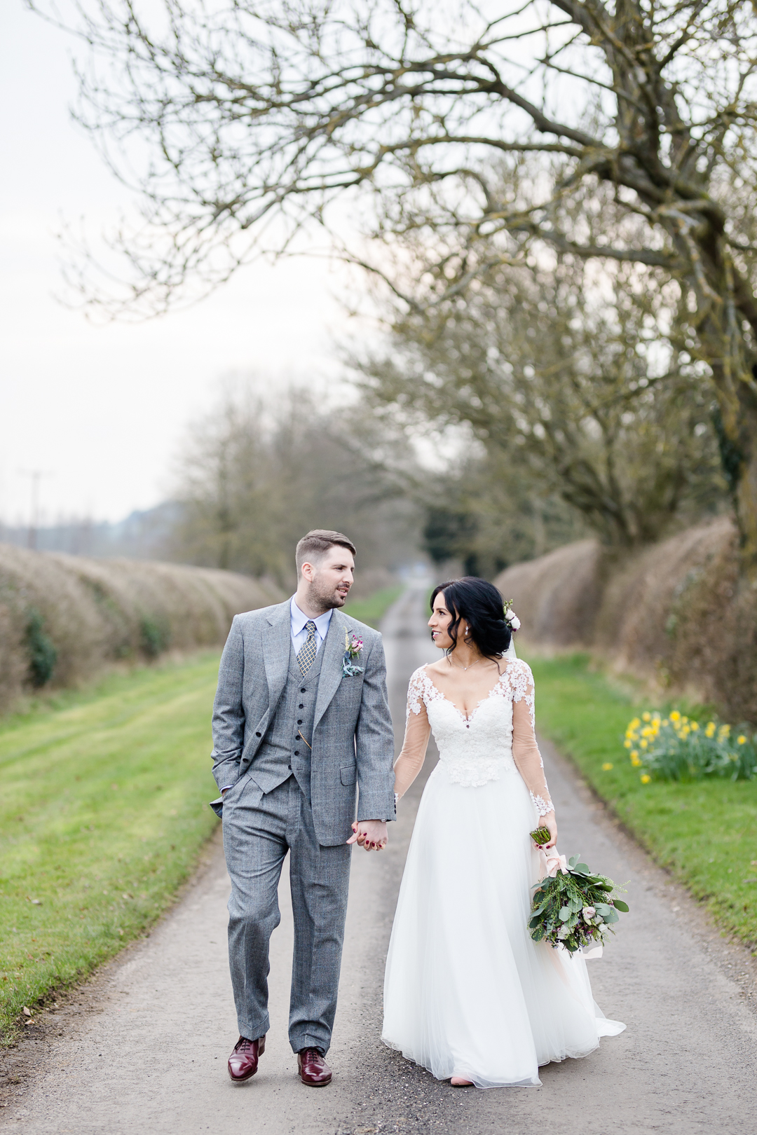 bride and groom walking down lane at Clock Barn Hampshire