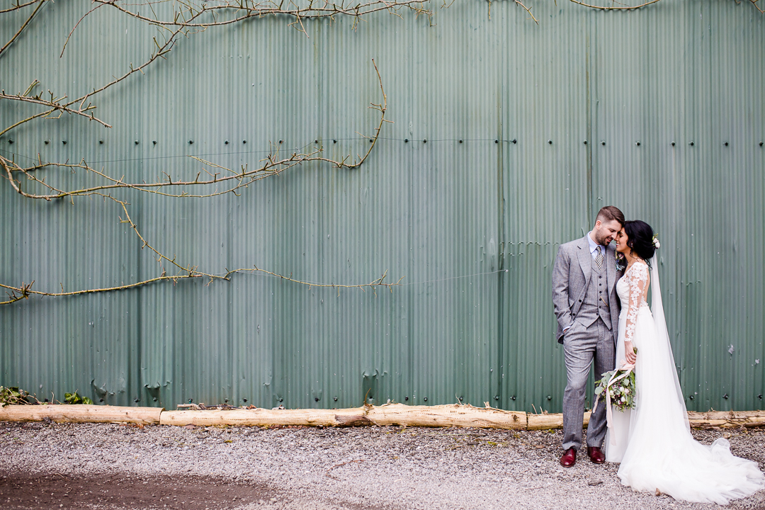 bride and groom standing in front of a green wall