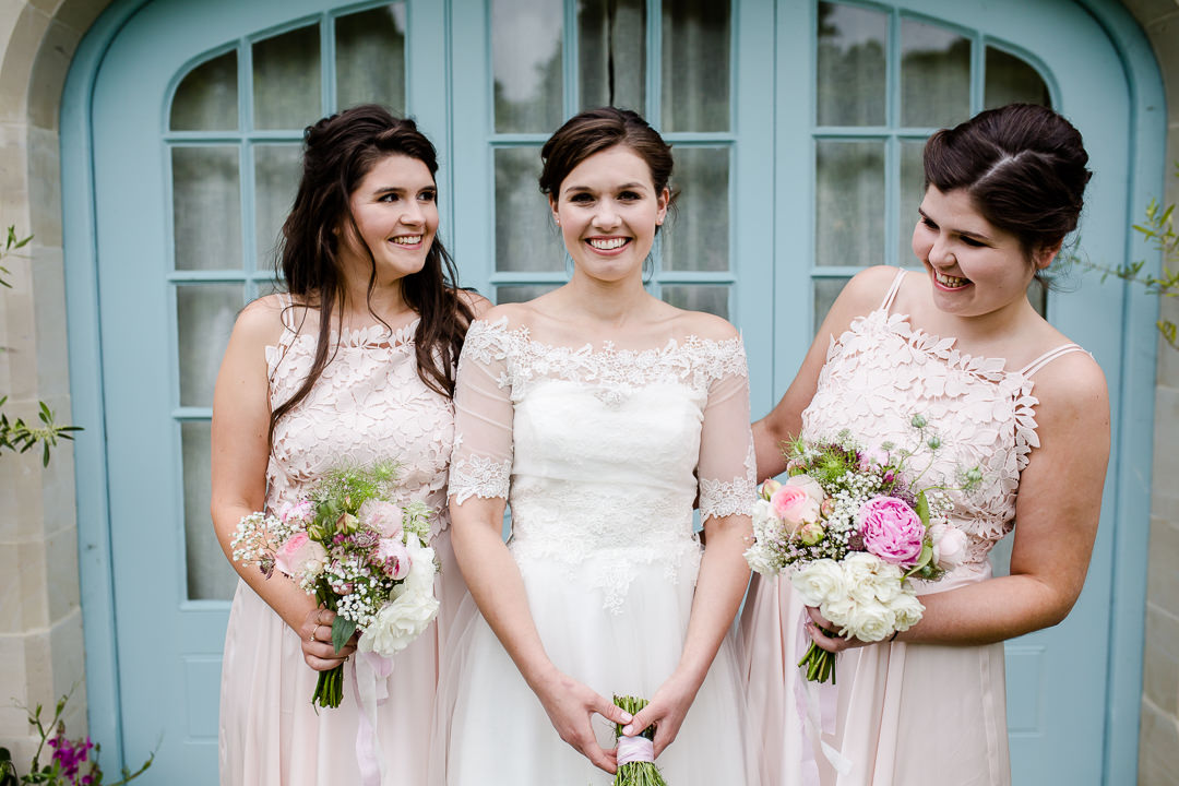 bride and bridesmaids laughing in front of blue door photo by Lydia Stamps Photography