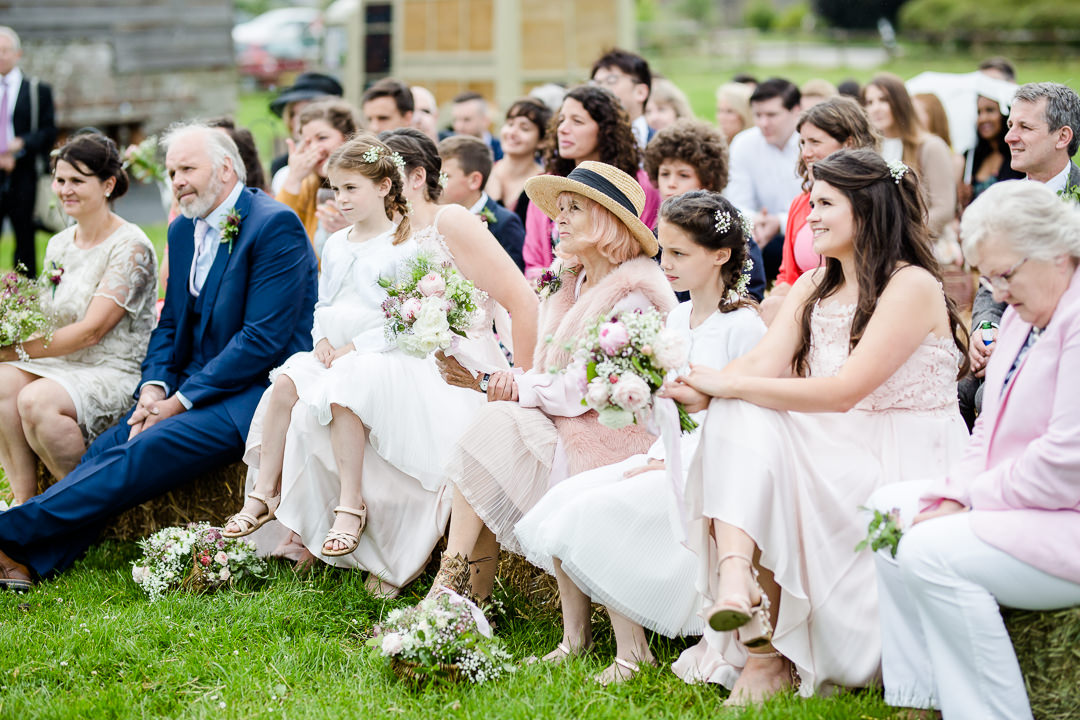 wedding guests watching outdoor wedding ceremony at Bowerchalke Barn Salisbury photo by Lydia Stamps Photography