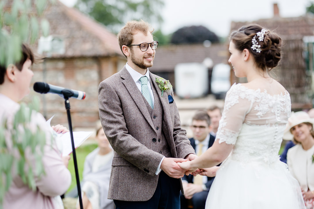 groom in tweed suit during wedding ceremony photo by Lydia Stamps Photography