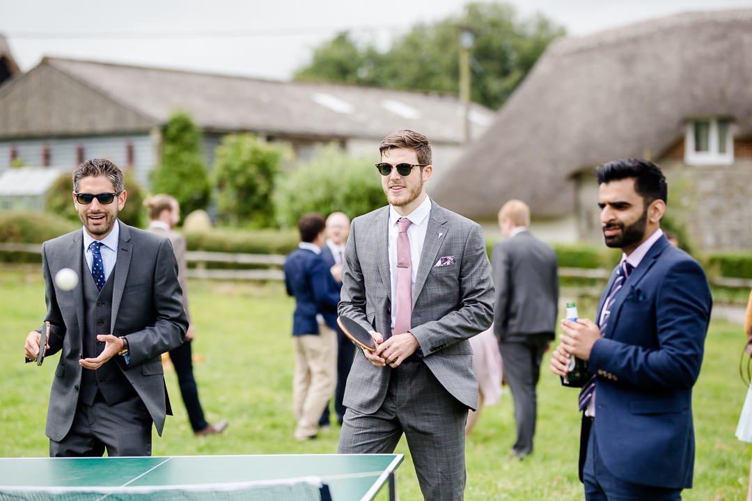 wedding guests playing ping pong outdoors