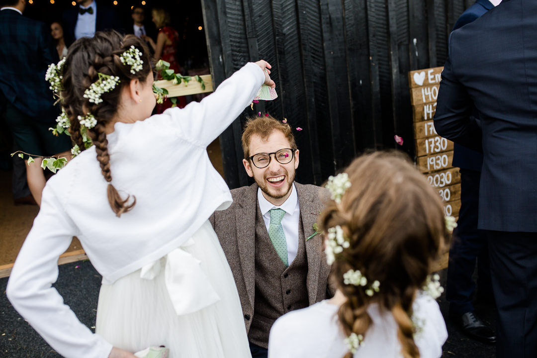 flower girls throwing confetti over grooms head