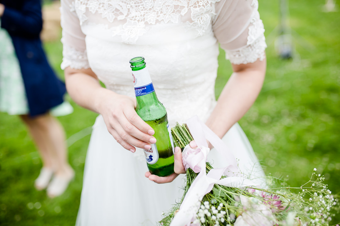 bride holding a beer and a bouquet