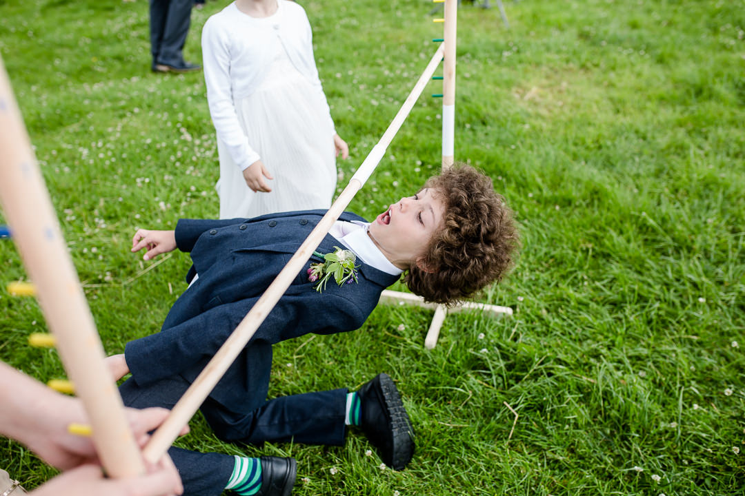 child playing limbo at wedding reception