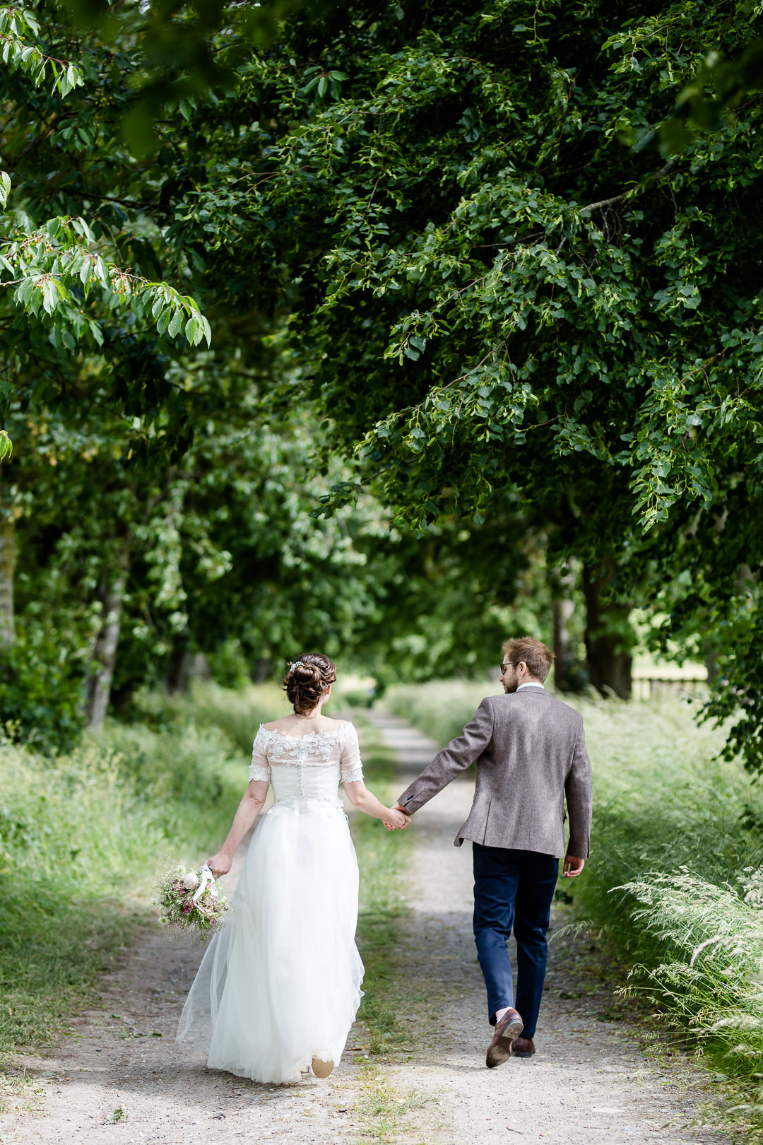 bride and groom walking down lane at bowerchalke barn near salisbury wiltshire