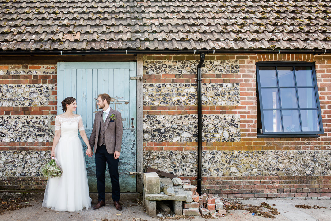 bride and groom in front of rustic blue door